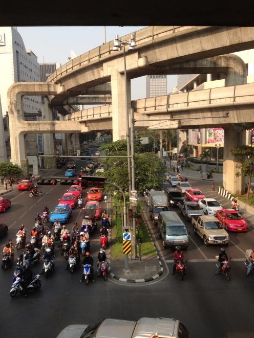 Het verkeer in Bangkok is onbeschrijfelijk. Overal hoor en zie je bussen, auto's, scooters en tuk-tuks. Iedereen in het verkeer is min of meer gemaskerd tegen de smog. En je moet rennen voor je leven om over te steken.