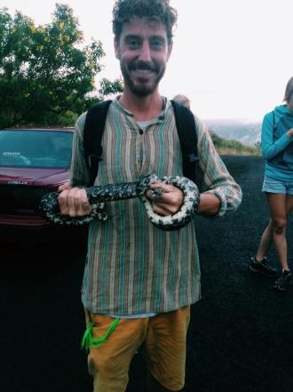 """Ron pakt de slang aan en gaat op de foto. De gids legt de slang in de bosjes waarop Ron zegt: """"Oh, was het een wilde?""""."""